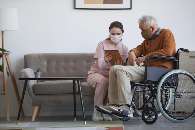 Volledig portret van jonge vrouwelijke verpleegster die senior man in rolstoel bijstaat met behulp van digitale tablet in bejaardentehuis, beide met maskers, kopieer ruimte