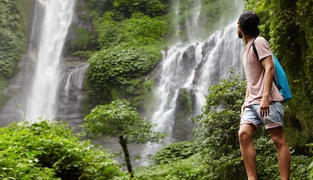 Volledig portret van jonge wandelaar of avonturier in spijkerbroek en snapback die van de natuur geniet