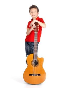 Volledig portret van kaukasische jongen met akoestische gitaar die op wit wordt geïsoleerd