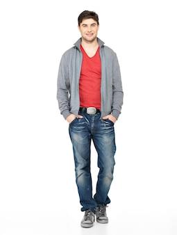 Volledig portret van lachende gelukkig knappe man in grijze jas, blauwe spijkerbroek. mooie kerel status geïsoleerd op wit