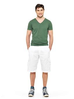 Volledig portret van lachende gelukkig knappe man in witte korte broek en groen t-shirt op wit wordt geïsoleerd