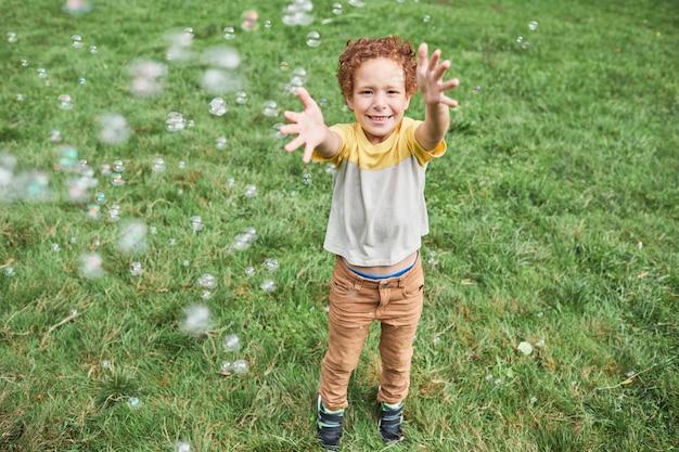 Volledig portret van lachende schattige jongen die met bubbels speelt terwijl hij buiten geniet van een verjaardagsfeestje...