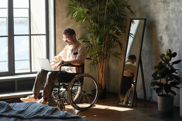 Volledig portret van moderne jongeman in rolstoel met laptop thuis verlicht door zonlicht in designinterieur, kopieer ruimte