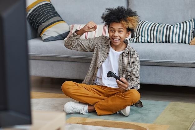 Volledig portret van opgewonden afro-amerikaanse jongen die thuis videogames speelt en gamepad vasthoudt terwijl hij op de vloer zit, kopieer ruimte