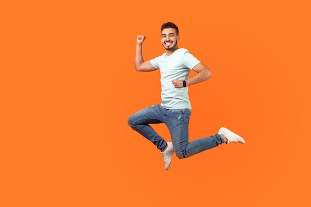 Volledig portret van positief geïnspireerde brunette man met baard in sneakers, denim outfit die in de lucht springt of snel snel rent. indoor studio-opname geïsoleerd op een oranje achtergrond, lege kopie ruimte