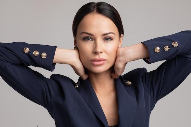 Volledig portret van prachtige brunette met make-up en golvend kapsel, gekleed in een elegant zwart kantoorpak en hoge hakken over grijze achtergrond. isoleren.