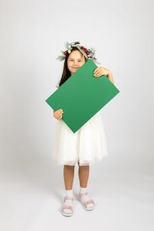 Volledig portret van schattig meisje in kerstkrans en in witte feestelijke jurk met groene blanco ...