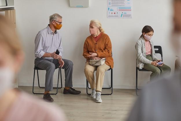 Volledig portret van senior koppel dat maskers draagt tijdens het wachten in de rij bij de kliniek of het vaccinatiecentrum, kopieer ruimte