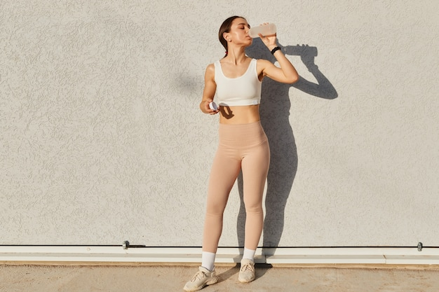 Volledig portret van slanke vrouw met perfect lichaam met witte top en beige leggins