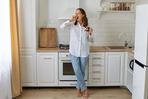 Volledig portret van slaperige vrouw die 's ochtends hete koffie drinkt, met een kopje in de handen staat en geeuwen, heeft energie nodig, draagt een wit overhemd en een spijkerbroek.
