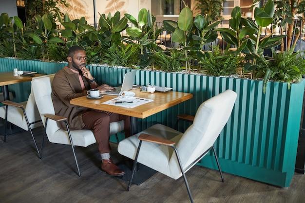 Volledig portret van succesvolle afro-amerikaanse zakenman die met laptop werkt terwijl hij aan tafel zit in een milieuvriendelijk groen café-interieur, kopieer ruimte