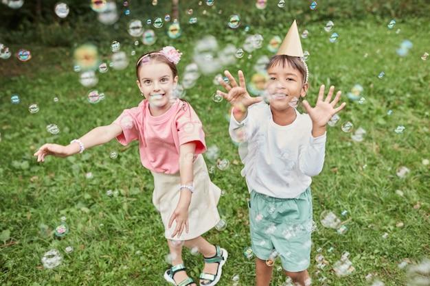 Volledig portret van twee schattige meisjes die met bubbels spelen terwijl ze buiten genieten van een verjaardagsfeestje...