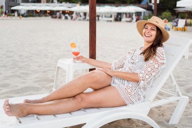 Volledig schot gelukkige vrouw die op zonnebank legt