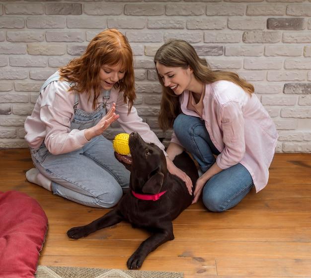 Volledig schot gelukkige vrouwen en hond op vloer