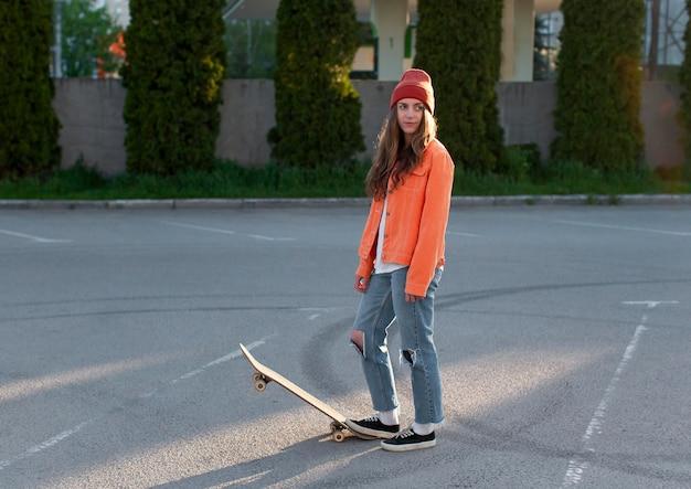 Volledig schot jong meisje met skateboard buitenshuis