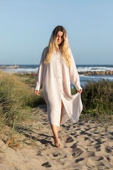 Volledig schot met jurk op het strand