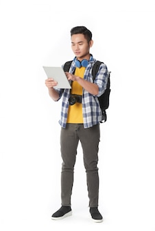 Volledig schot van de jonge aziatische mens die het digitale stootkussen gebruikt