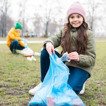 Volledig schot van glimlachend meisje recycling