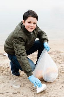 Volledig schot van glimlachende jongen met plastic zak