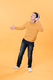 Volledig schot van jongen die aan muziek met hoofdtelefoons luistert