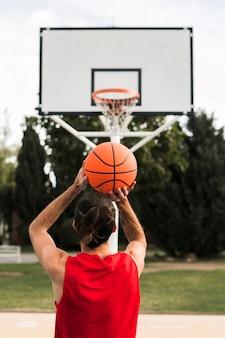Volledig schot van jongen die in de basketbalhoepel werpt