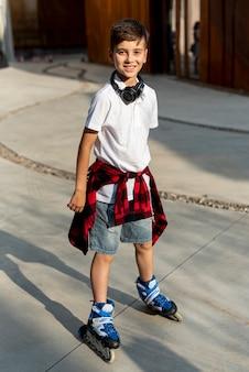 Volledig schot van jongen met blauwe rolbladen