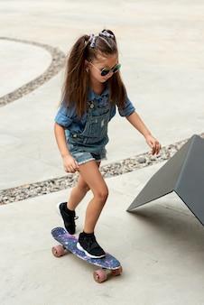 Volledig schot van kind op skateboard