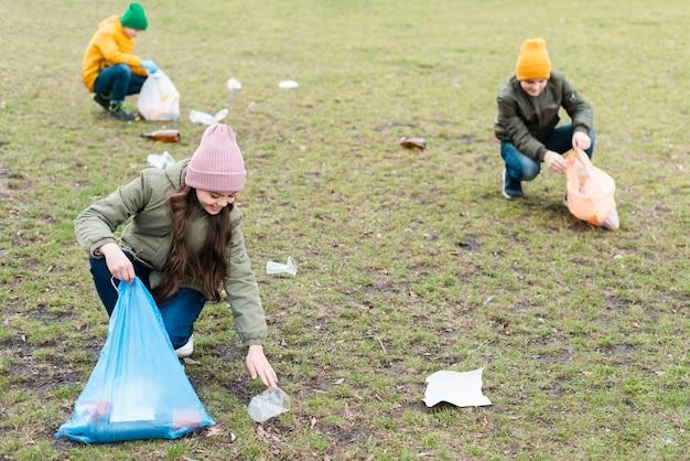 Volledig schot van kinderen die de grond schoonmaken