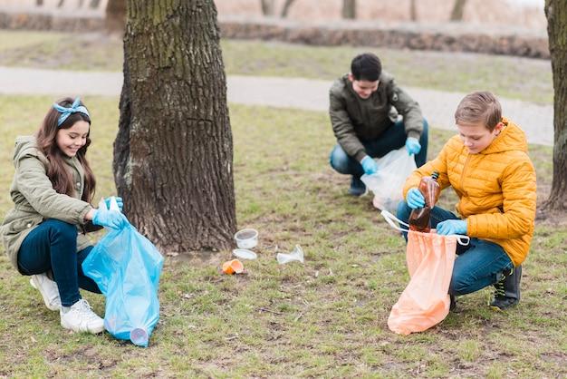 Volledig schot van kinderen met plastic zakken