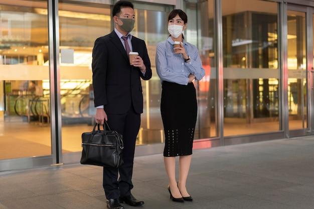 Volledig schot van man en vrouw die gezichtsmasker dragen