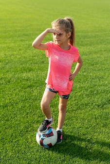 Volledig schot van meisje met roze t-shirt en bal
