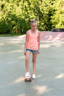 Volledig schot van meisje met skateboard
