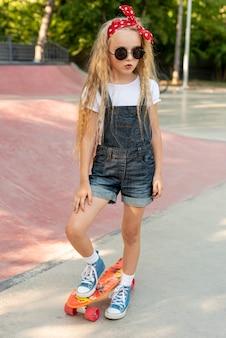 Volledig schot van meisje op skateboard