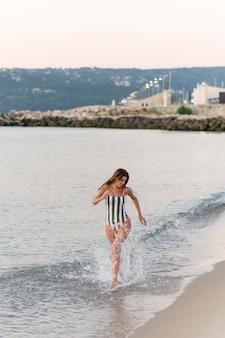 Volledig schot van mooi meisje bij strand