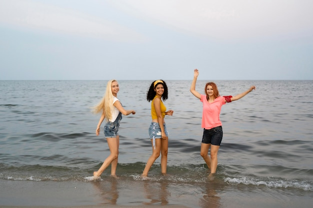 Volledig schot van mooie vrienden bij strand