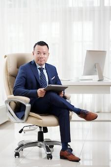 Volledig schot van succesvolle aziatische directeur zittend in kleermakerszit op zijn luxe baas stoel in lichte ruime kantoor