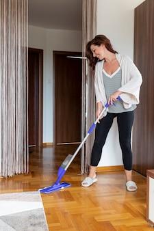 Volledig schot van vrouw die de vloer schoonmaakt