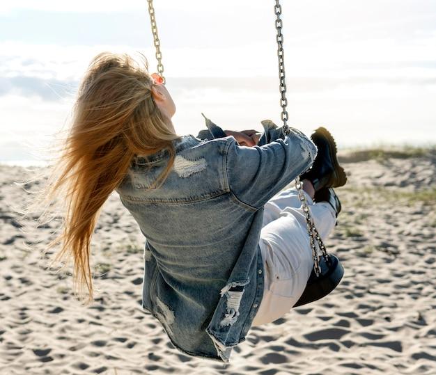Volledig schot vrouw op schommel op het strand