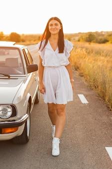 Volledig schot vrouw poseren in de buurt van auto