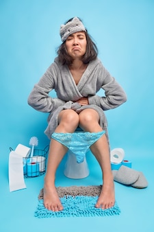 Volledig shot van ontevreden brunette aziatische vrouw lijdt aan buikkrampen