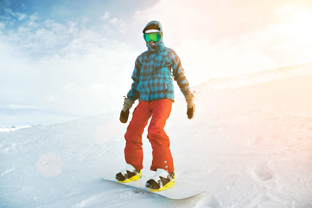 Volledig uitgerust en bedekt met een koude beginnende snowboarder draagt een sneeuwbril en poseert op de top van de berg