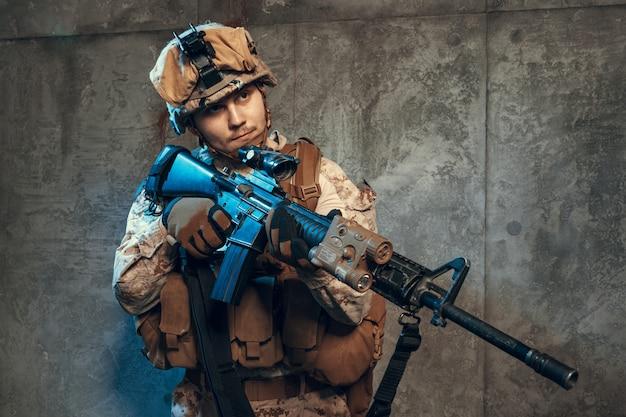 Volledig uitgeruste leger-soldaat in camo-uniform en helm, gewapend met pistool en aanvalswapen