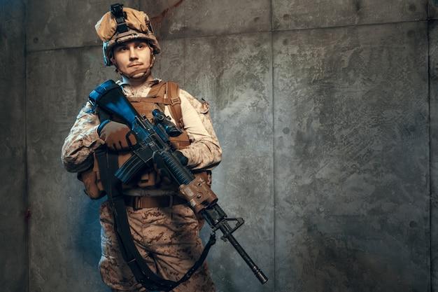 Volledig uitgeruste leger soldaat in camo-uniform en helm, gewapend met pistool en aanvalswapen