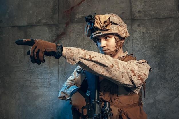 Volledig uitgeruste legermilitair in camouflagepak en helm, gewapend met pistool en aanvalsgeweer