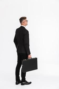 Volledig zijaanzichtportret van een knappe zelfverzekerde zakenman die een pak draagt dat geïsoleerd staat en een aktetas draagt