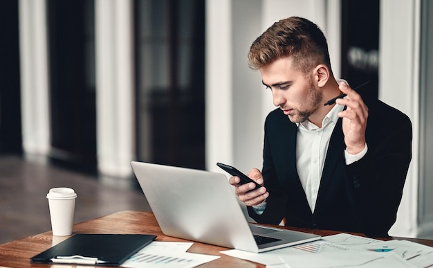Volledige concentratie. een jonge zakenman zit in een zakencentrum met een laptop en een telefoon in zijn hand, op tafel liggen documenten en koffie