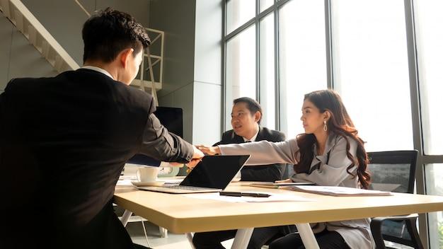 Volledige concentratie op het werk. groep jonge en bedrijfsmensen die terwijl het zitten bij het bureau samen met collega's die op de achtergrond zitten werken communiceren