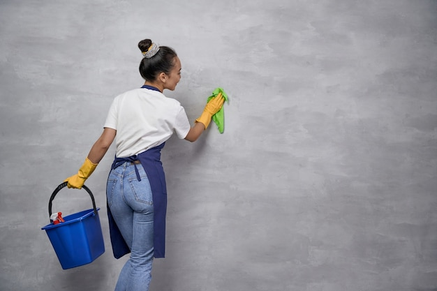 Volledige desinfectie. achteraanzicht van huisvrouw of meid vrouw uniform en gele rubberen handschoenen met emmer met verschillende schoonmaakproducten en grijze muur schoonmaken. huishoudelijke en schoonmaakdiensten