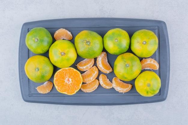 Volledige donkere snijplank van zure mandarijnen op witte achtergrond. hoge kwaliteit foto