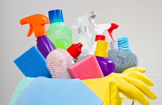 Volledige doos met schoonmaakproducten en -handschoenen geïsoleerd op wit